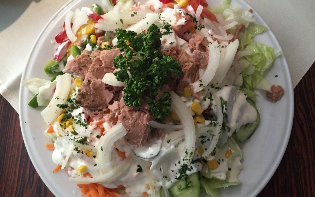 Salatteller mit Thunfisch, Zwiebelringen und Oliven